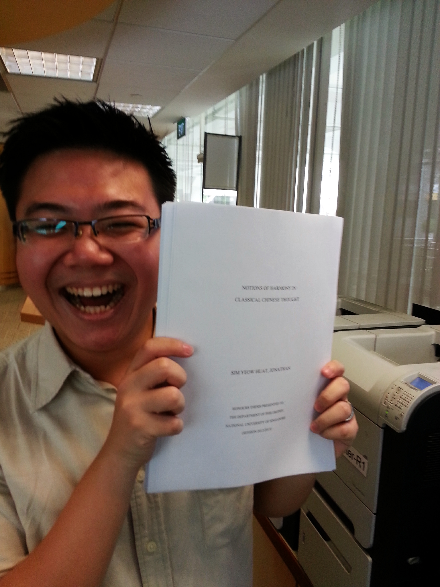 Proudly displaying the printed thesis! Notice the disheveled hair from the many overnight editing/writing marathons.